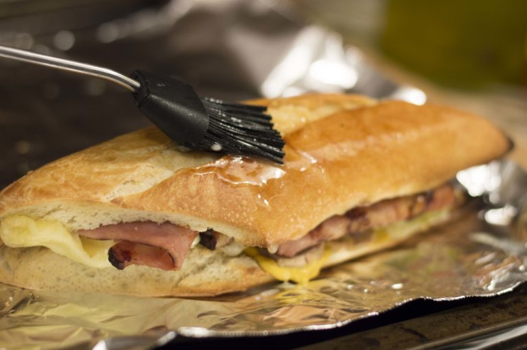 Spreading delicious melted butter over the cubano sandwich