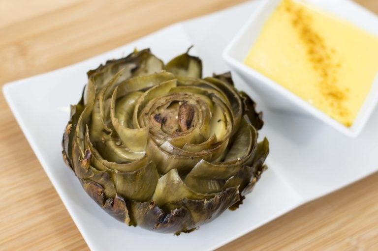 whole roasted artichokes server with a side of hollandaise