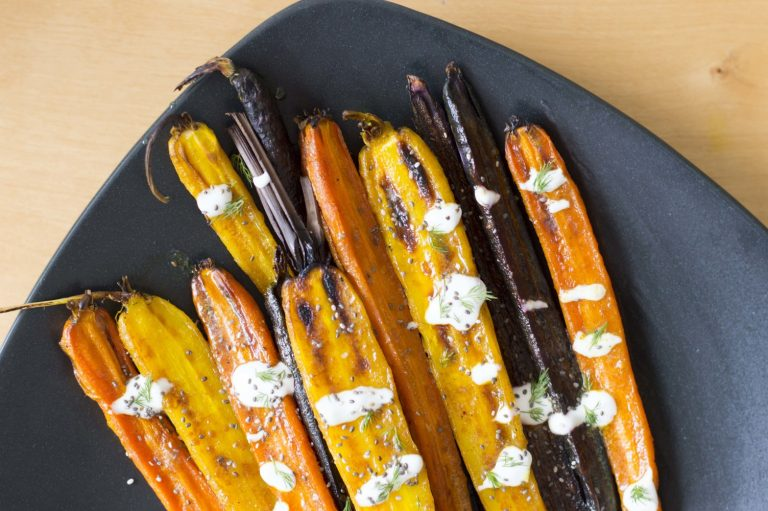 Top down photo of the turmeric glazed rainbow carrots with dill sauce
