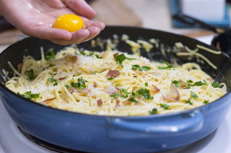 Adding the egg yolk to the carbonara to finish the dish off