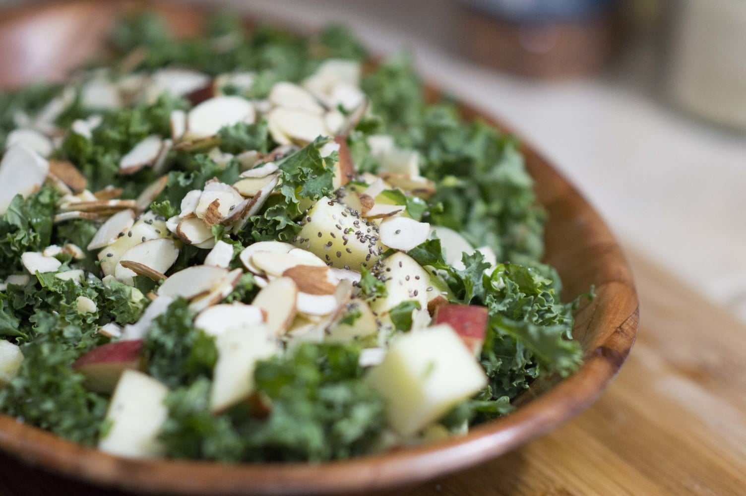 chopped kale apple salad topped with almonds and chia seeds