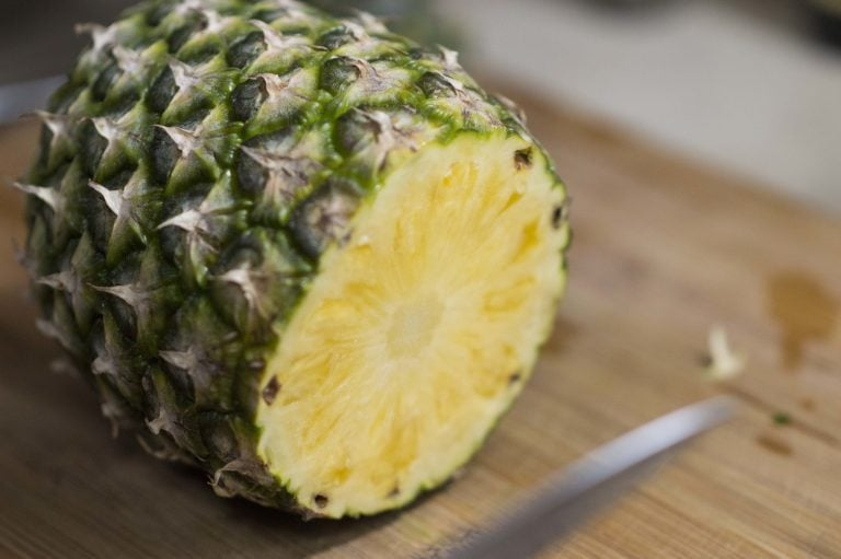 The bottom has been removed to show you how to cut a pineapple