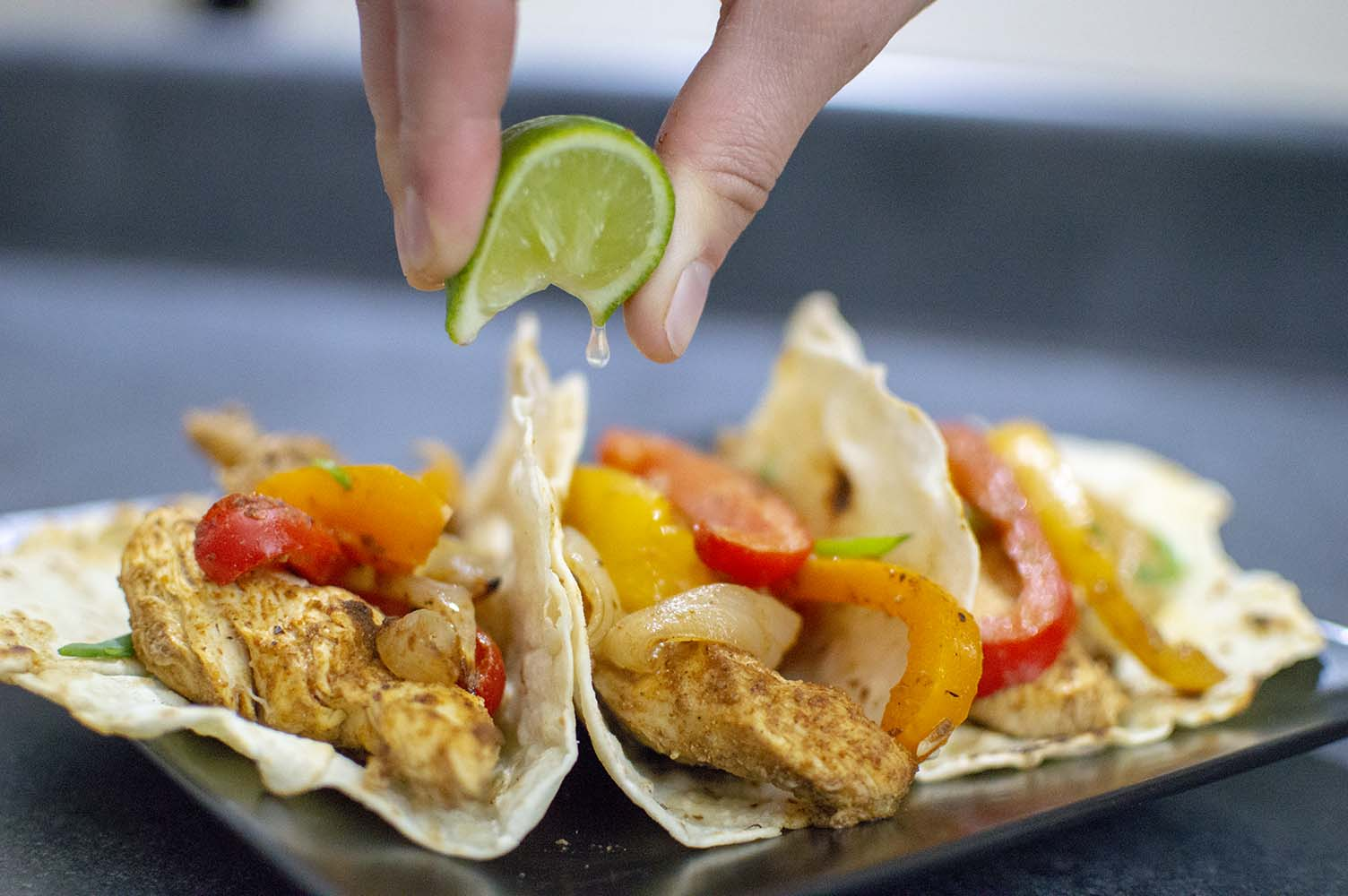 Sheet Pan Chicken Fajitas dished up on tortillas and ready to eat